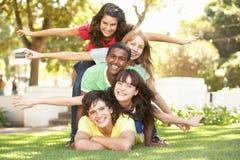 Grupo de adolescentes llenados para arriba en parque Imagen de archivo