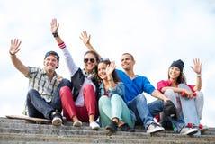 Grupo de adolescentes que agitan las manos Imagenes de archivo