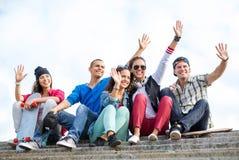 Grupo de adolescentes que agitan las manos Fotografía de archivo