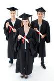 Grupo de adolescentes que comemoram após a graduação imagem de stock