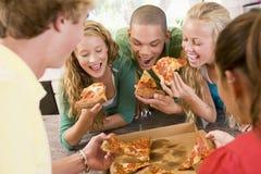 Grupo de adolescentes que comen la pizza Fotos de archivo libres de regalías