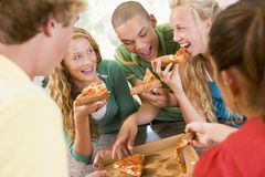 Grupo de adolescentes que comen la pizza Foto de archivo libre de regalías