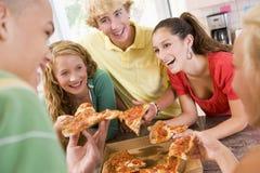 Grupo de adolescentes que comen la pizza Imagen de archivo
