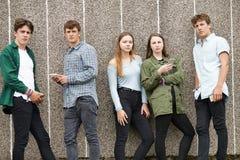 Grupo de adolescentes que comparten el mensaje de texto en los teléfonos móviles Imagenes de archivo