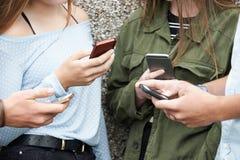 Grupo de adolescentes que comparten el mensaje de texto en los teléfonos móviles Imagen de archivo