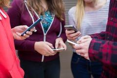 Grupo de adolescentes que comparten el mensaje de texto en los teléfonos móviles Fotos de archivo libres de regalías