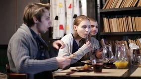 Grupo de adolescentes que comparten la comida junto en café metrajes