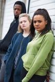 Grupo de adolescentes que cuelgan hacia fuera en el ambiente urbano imagenes de archivo