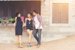 Grupo de adolescentes que cuelgan hacia fuera en el ambiente urbano, HOL del verano Fotografía de archivo
