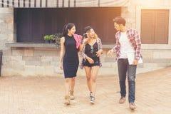 Grupo de adolescentes que cuelgan hacia fuera en el ambiente urbano, HOL del verano Imagenes de archivo
