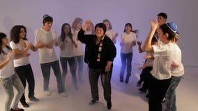 Grupo de adolescentes que dançam com uma senhora superior vídeos de arquivo