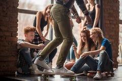 Grupo de adolescentes que hacen diverso sentarse de las actividades Foto de archivo libre de regalías