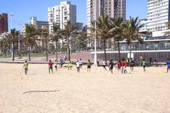 Grupo de adolescentes que juegan a fútbol en la playa Foto de archivo