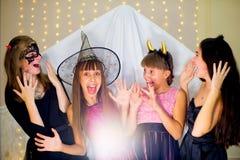 Grupo de adolescentes que llevan el miedo de los disfraces de Halloween del fantasma Fotografía de archivo