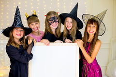 Grupo de adolescentes que llevan los disfraces de Halloween que presentan con blanco Imágenes de archivo libres de regalías