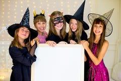 Grupo de adolescentes que llevan los disfraces de Halloween que presentan con blanco Fotografía de archivo