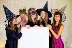 Grupo de adolescentes que llevan los disfraces de Halloween que presentan con blanco Foto de archivo libre de regalías