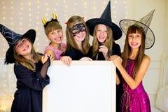 Grupo de adolescentes que llevan los disfraces de Halloween que presentan con blanco Foto de archivo
