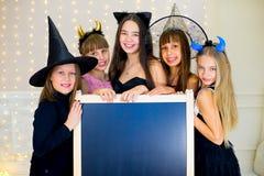 Grupo de adolescentes que llevan los disfraces de Halloween que presentan con negro Fotografía de archivo libre de regalías