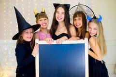 Grupo de adolescentes que llevan los disfraces de Halloween que presentan con negro Foto de archivo libre de regalías