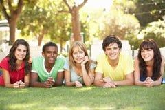 Grupo de adolescentes que mienten en los estómagos en parque Imagen de archivo libre de regalías
