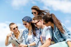 Grupo de adolescentes que miran el ordenador de la PC de la tableta Imágenes de archivo libres de regalías