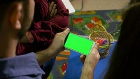 Grupo de adolescentes que miran el teléfono elegante con la pantalla verde en un taller almacen de video
