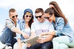 Grupo de adolescentes que miran la PC de la tableta Fotografía de archivo libre de regalías