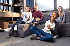 Grupo de adolescentes que miran película junto en casa, adolescentes que tienen concepto de la diversión Imagen de archivo libre de regalías