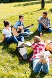 grupo de adolescentes que passam o tempo junto e que escutam fotografia de stock