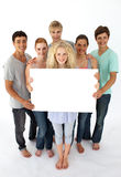 Grupo de adolescentes que prendem um cartão em branco fotografia de stock royalty free