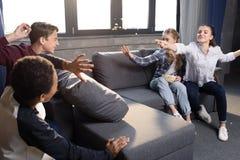 Grupo de adolescentes que se divierten con palomitas en casa Foto de archivo libre de regalías