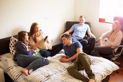 Grupo de adolescentes que se relajan en dormitorio Imagen de archivo