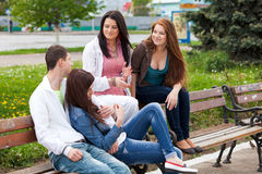 Grupo de adolescentes que se sientan afuera Foto de archivo