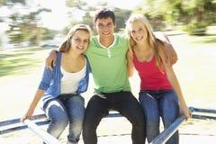 Grupo de adolescentes que se sientan en cruce giratorio del patio Foto de archivo libre de regalías