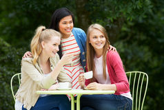 Grupo de adolescentes que se sientan en el café al aire libre Fotografía de archivo libre de regalías
