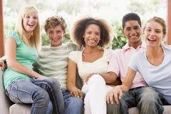 Grupo de adolescentes que se sientan en un sofá Imagen de archivo libre de regalías