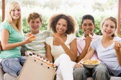 Grupo de adolescentes que se sientan en un sofá Imágenes de archivo libres de regalías