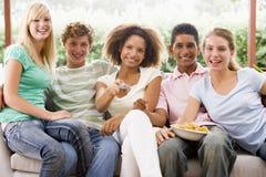 Grupo de adolescentes que se sientan en un sofá Fotografía de archivo