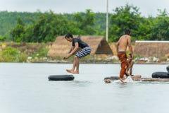 Grupo de adolescentes que se zambullen en el agua en el río Foto de archivo