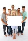 Grupo de adolescentes que sostienen una tarjeta en blanco Fotografía de archivo libre de regalías