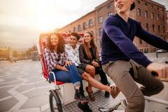 Grupo de adolescentes que viajan en el triciclo Imagen de archivo libre de regalías
