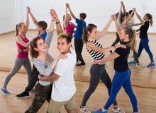 Grupo de adolescentes satisfechos que bailan tango en estudio de la danza Foto de archivo