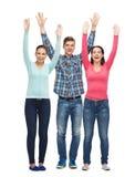 Grupo de adolescentes sonrientes con las manos aumentadas Imagen de archivo libre de regalías