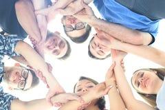 Grupo de adolescentes sonrientes con las manos encima de uno a Fotografía de archivo libre de regalías
