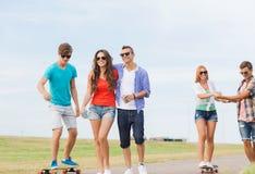 Grupo de adolescentes sonrientes con los monopatines Imagen de archivo libre de regalías