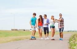 Grupo de adolescentes sonrientes con los monopatines Foto de archivo libre de regalías