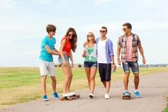 Grupo de adolescentes sonrientes con los monopatines Imagen de archivo