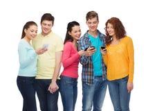 Grupo de adolescentes sonrientes con smartphones Foto de archivo libre de regalías