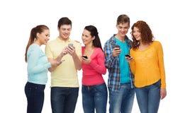 Grupo de adolescentes sonrientes con smartphones Imagen de archivo libre de regalías